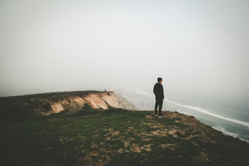 崖の上で遠くを眺めながらたたずむ男性