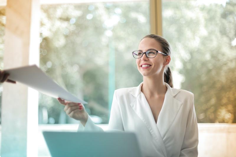 笑顔で書類を受け取るメガネをかけたオフィスで働く女性