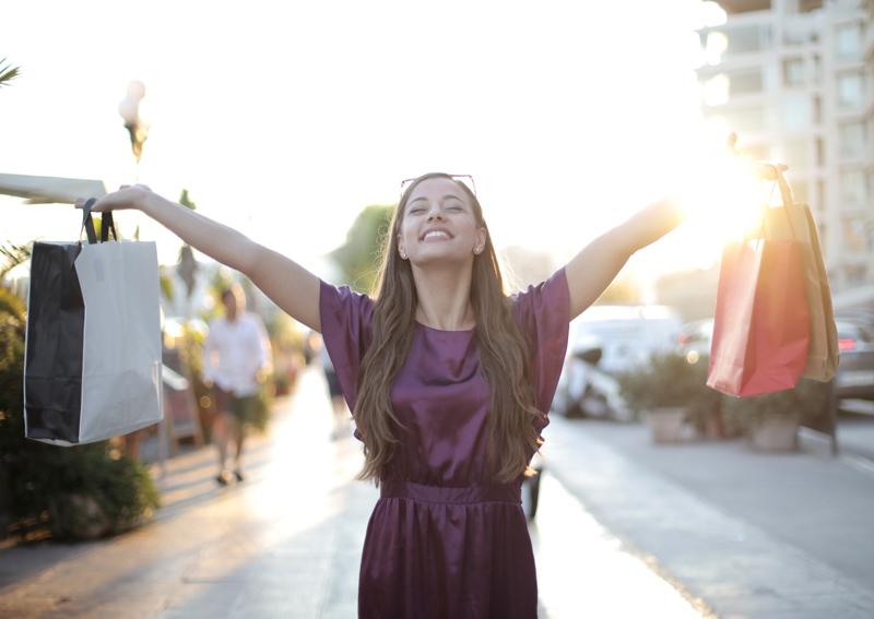 紙袋を両手に持ち笑顔で嬉しそうにする女性