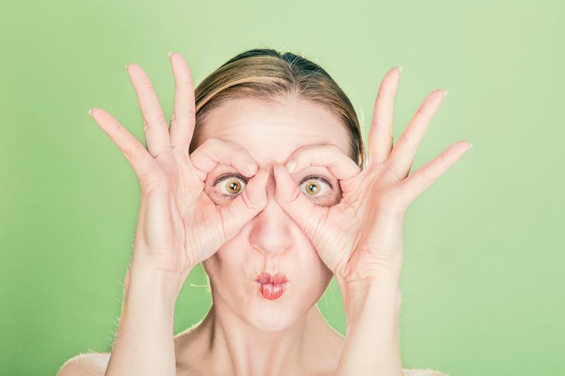 両手でメガネの形を作りこちらを目を見開いて覗き込む女性