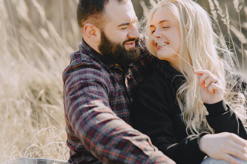 男性に後ろから抱きしめられながら笑顔で座る女性