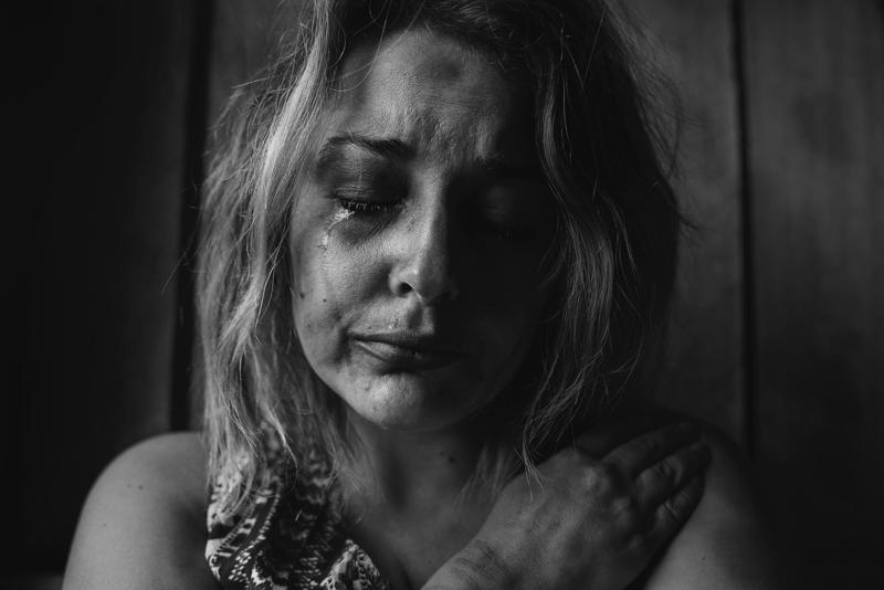 自分を抱きしめながら涙を流す女性