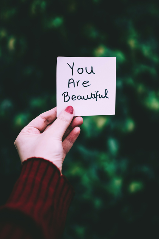 You are beatifulと書かれた紙を持つ女性の手