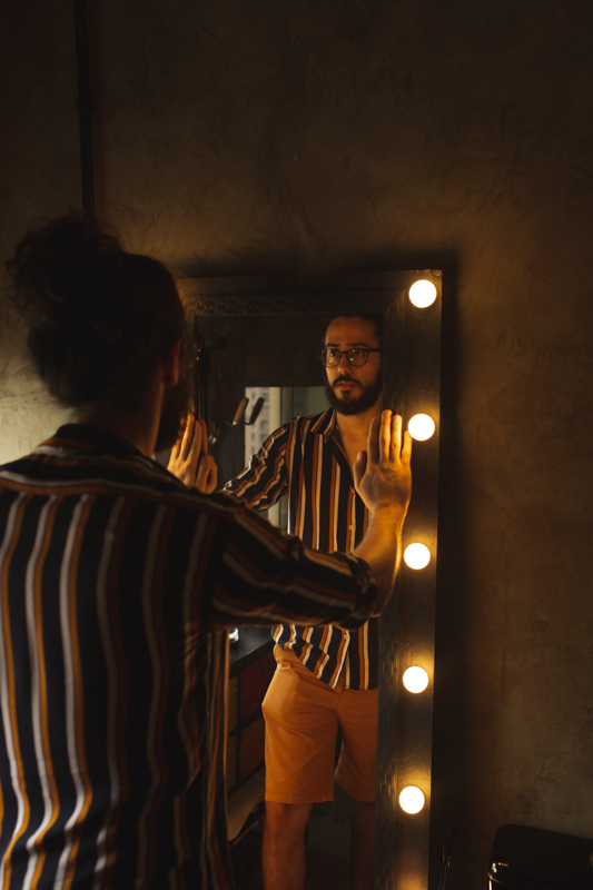 自分の姿をライト付きの大きな姿見で見つめて思い詰める男性