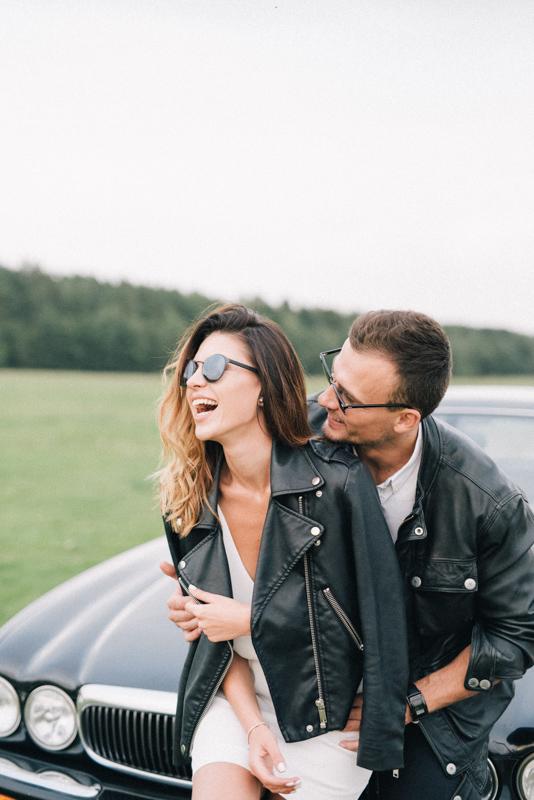 車のボンネットに男性と一緒に座りながら触られくすぐったそうに笑う女性