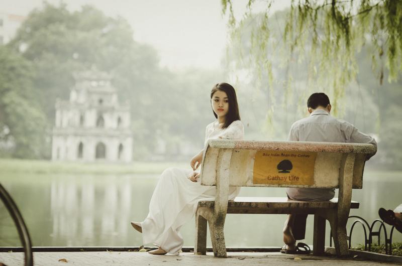 ベンチに座る男性と後ろを向きつまらなさそうにする女性