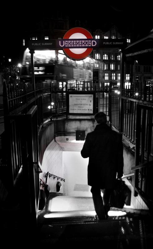 暗い夜に海外の地下鉄の駅の入り口を大きな荷物を持って下りるスーツ姿の男性