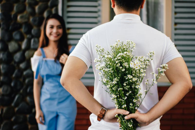 背中に白い花束を隠して笑顔の女性に会いにきた白いシャツ姿の男性