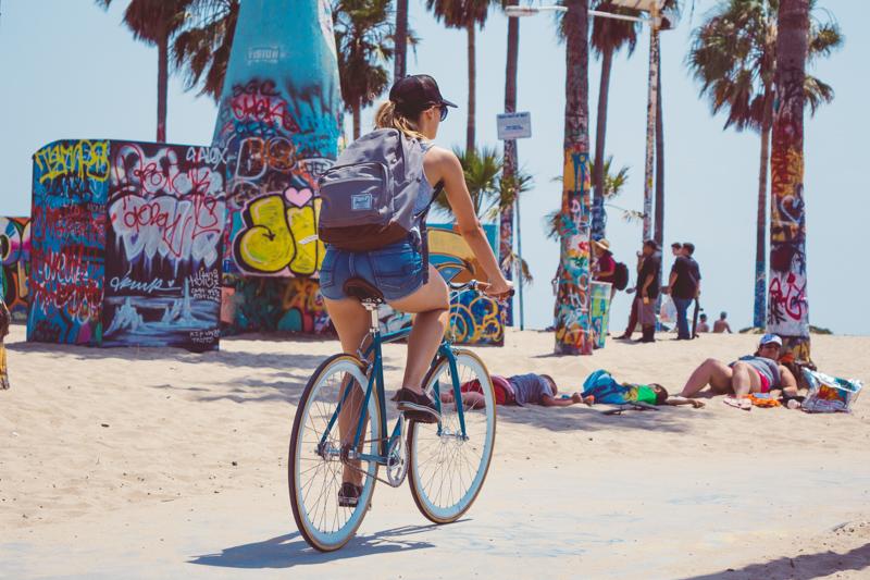 トロピカルな木々が立つ海岸でサイクリングする女性