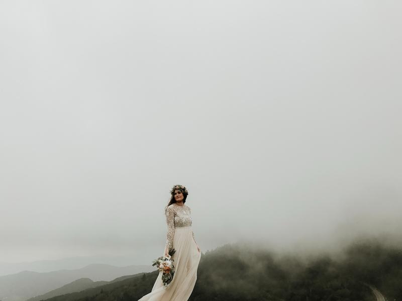 ウェディングドレスで花束を持ち崖にたたずむ女性
