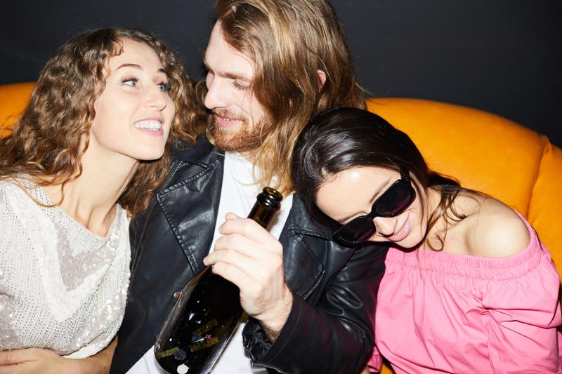 ソファに座り女性二人と楽しむ男性