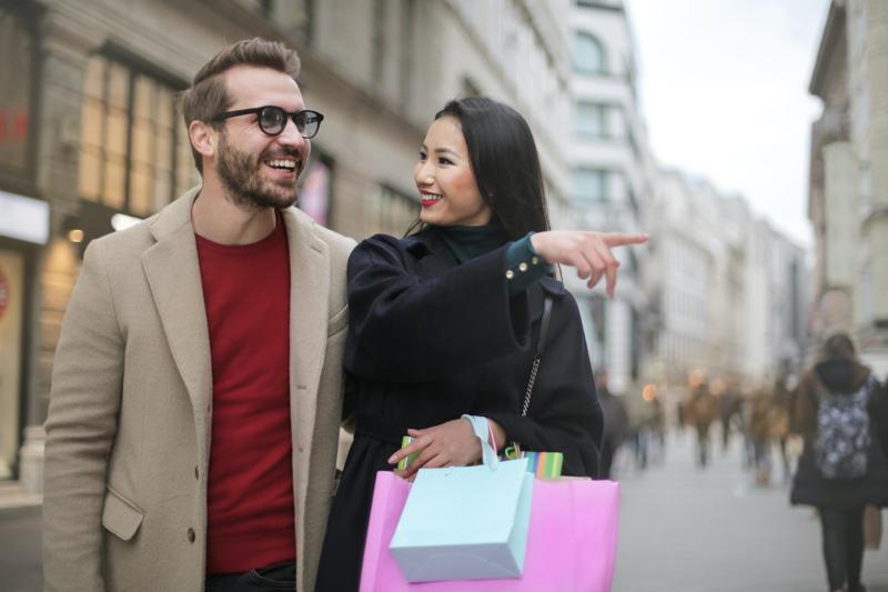 笑顔でショッピングを楽しむアジア系女性と西洋系男性のカップル
