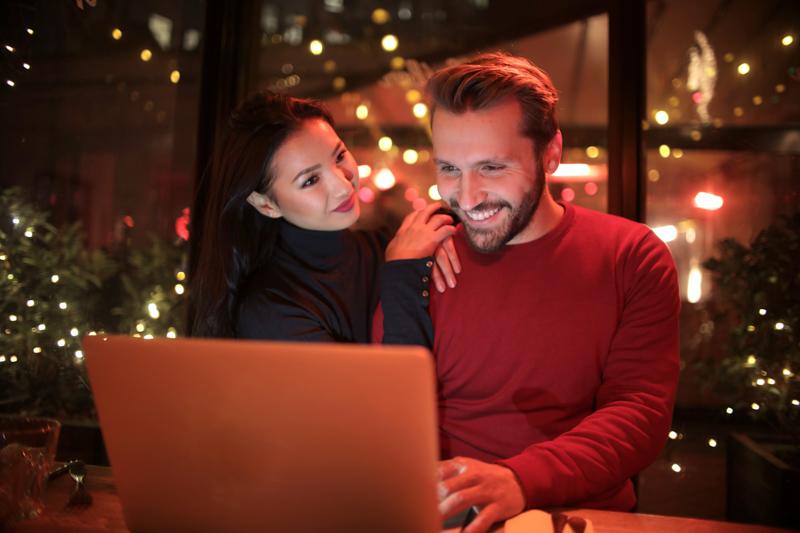 笑顔でパソコンを操作するアジア系女性と西洋系男性のカップル