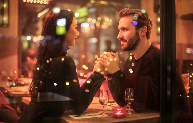 レストランで夕食を食べながら手を握り見つめ合うカップル