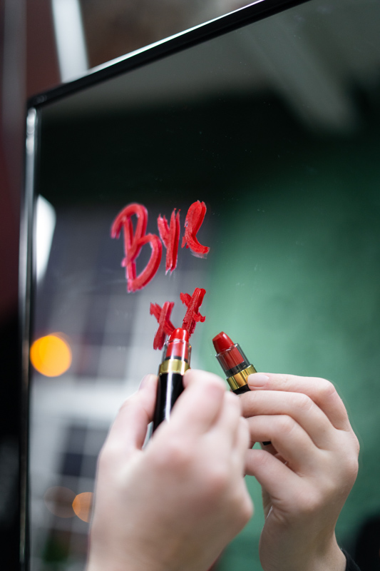 bye xxと口紅で鏡に書く女性