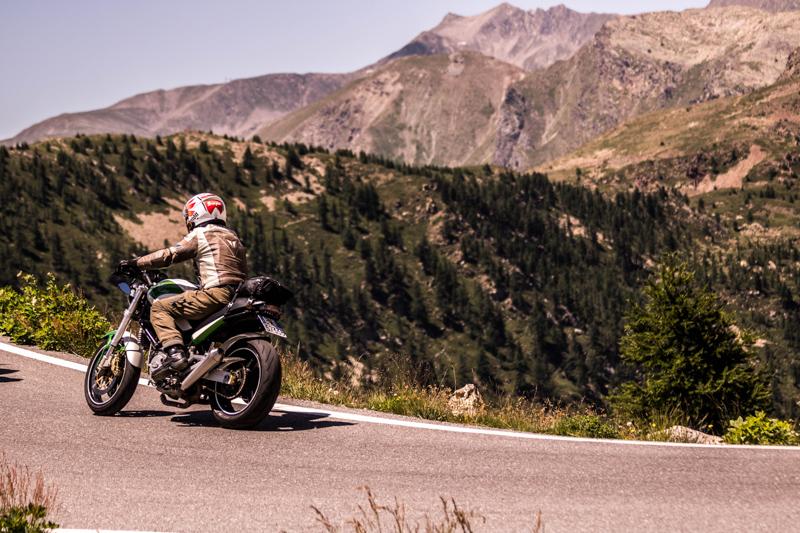 険しい山々の中疾走するバイク