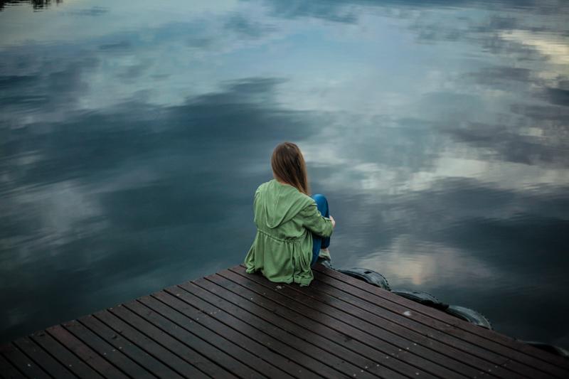 湖の桟橋の端に座り寂しそうにたたずむ女性