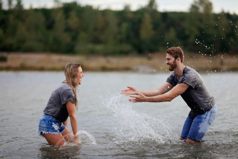 川で水をかけ合い楽しそうに遊ぶカップル