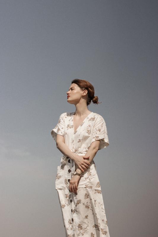青空の中でワンピースを着て遠くを眺める女性