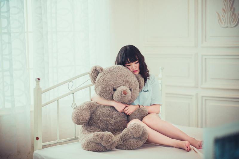 ベッドの上で大きな熊のぬいぐるみを抱きしめて寂しそうにする女性