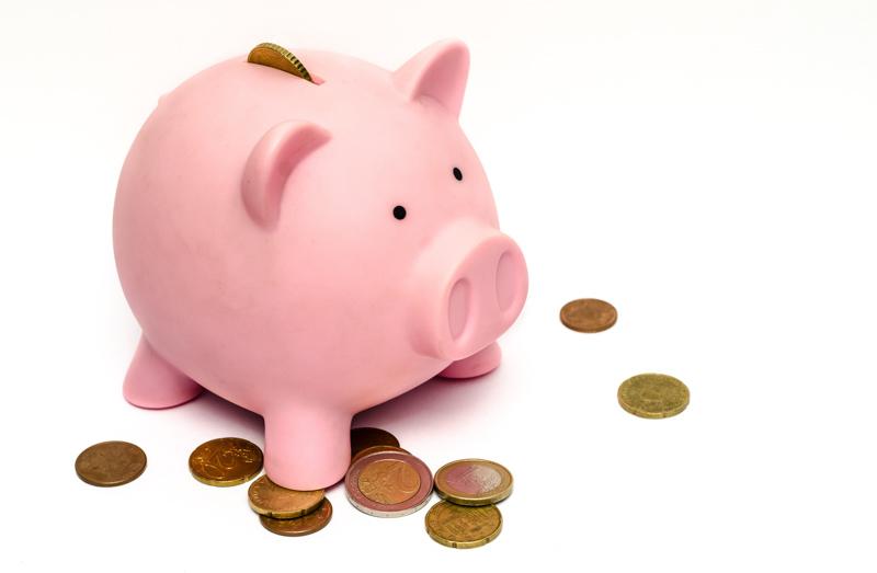 ぶたの貯金箱と周りに散らばった硬貨