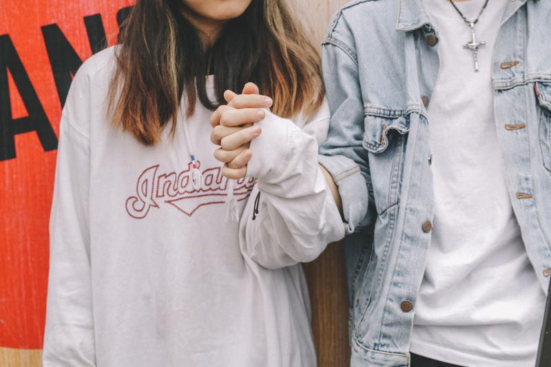 手を握り締め合うカジュアルな服装をしたカップル